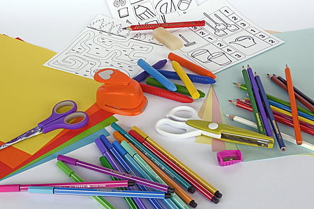 assorted-colored coloring pencils, scissors, sharpeners and papers on panel
