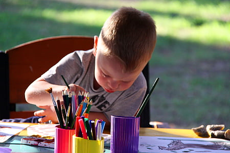 boy wearing grey shirt drawing on table with assorted color pencil