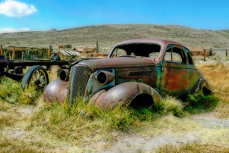 rusty Beetle car parked in middle of grass field
