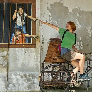 woman wearing green riding bicycle near wall art