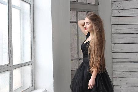 woman wearing black dress standing near window