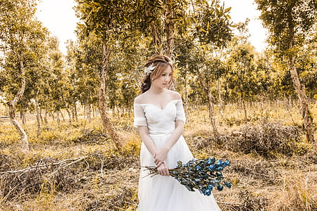woman standing on a grass field while holding a bouquet of blue flowers