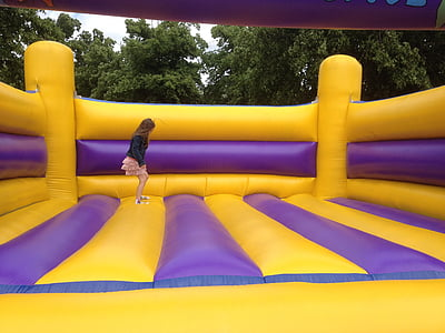 girl jumping on yellow and purple inflatable bouncer