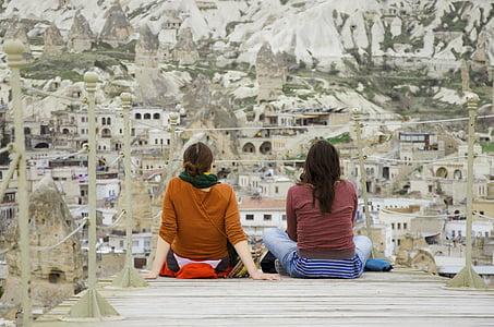 two women sitting on dock