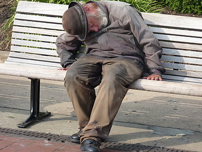 man in gray dress shirt and pants sleeping in gray wooden bench during daytime