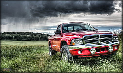 red Dodge truck on grass land under cloudy sky