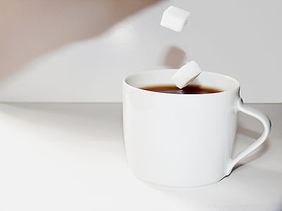 white ceramic teacup filled with black liquid and sugar cube