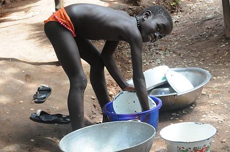 boy wearing brief washing dish during daytime