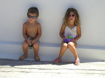 boy and girl sitting on white concrete edge