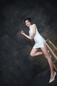 woman in white cheongsam sitting on stool