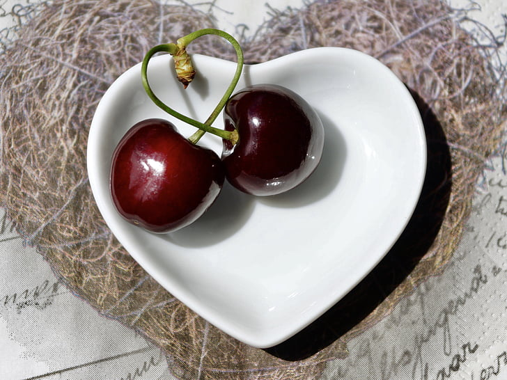 two cherries on white ceramic bowl