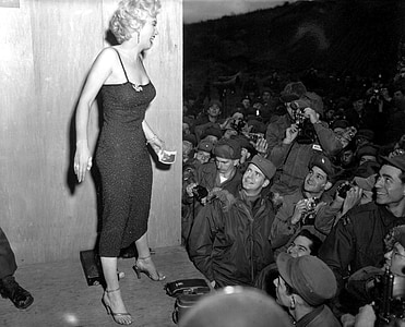 grayscale photo of Marilyn Monroe standing on stage in front of crowd