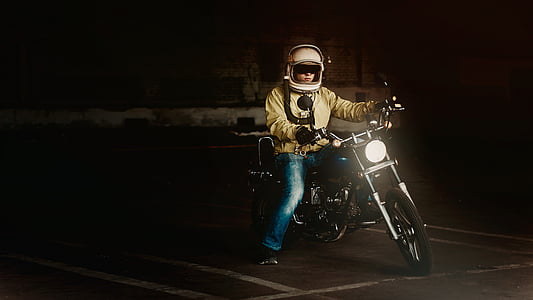man in yellow jacket and blue jeans riding on black motorcycle