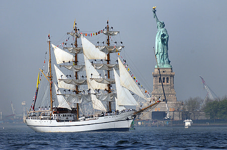 photo of white sailing ship near Statue of Liberty