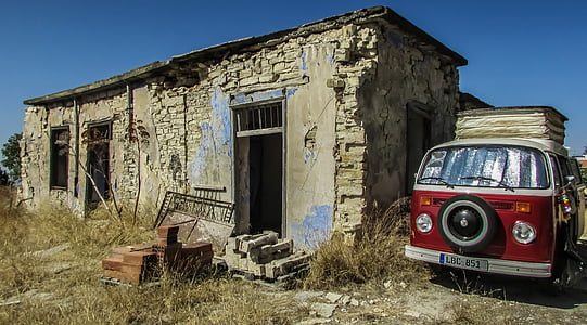 red bus beside concrete house