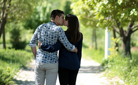 couple kissing each other between trees during daytime