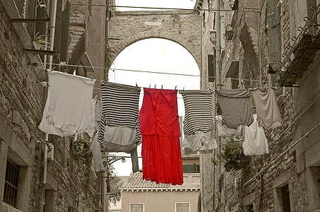 assorted-color clothes hanging between buildings