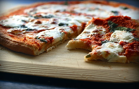 cooked pizza on brown wooden tray