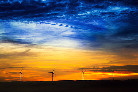 landscape photography of blue and yellow clouds in front of four windmills