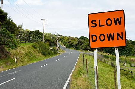 photo of asphalt road beside slow down signboard