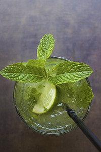 lemon juice with green leaves in clear glass cup