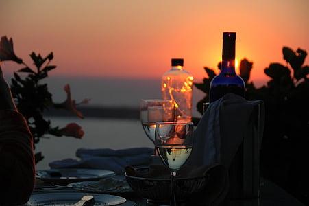 blue glass bottle near wine glass during sun set