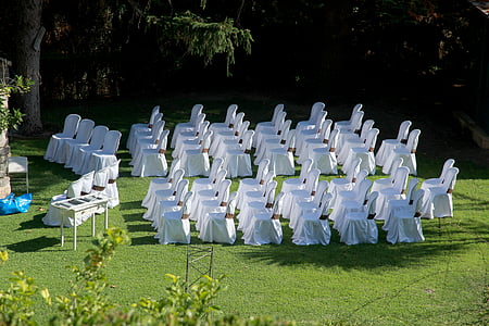 white covered chairs filed horizontally on green lawn