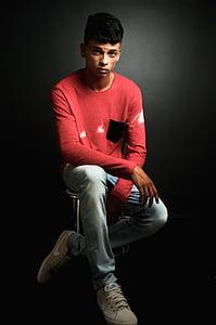 man wearing red sweatshirt sitting on chair