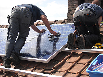 man putting solar panel board on roof during daytime