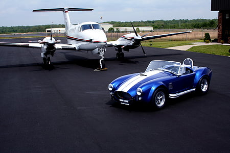 blue and white convertible near white airliner on road