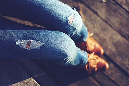 person wearing distressed blue fitted jeans