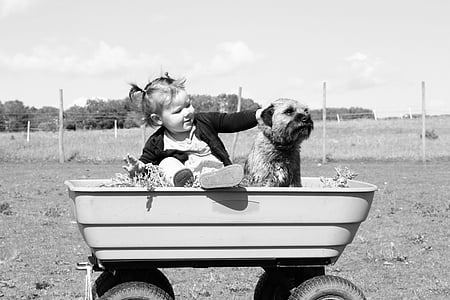 grayscale photo of child with dog on wagon