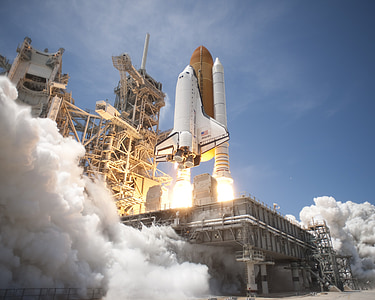 white and brown space shuttle launch under blue sky during daytime