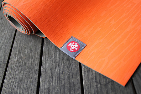 red yoga mat placed on gray board