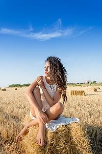 woman wearing sleeveless dress setting on hay