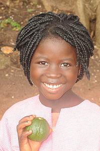 girl holding brown fruit