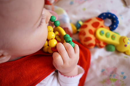 baby biting yellow and green toy