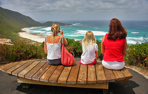 women sitting on brown wooden bench looking at ocean