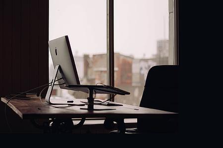 laptop on desk near window