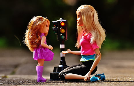 Barbie doll in front of baby doll in the middle of street