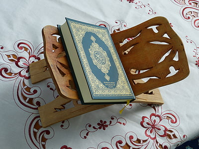 green and gold hardbound book and brown wooden holder