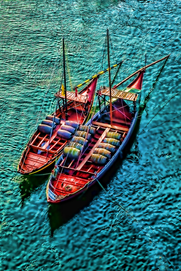 two red barrel boats on body of water painting