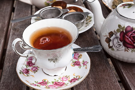white teacup with tea and spoon