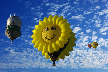 yellow sunflower hot air balloon under cloudy blue sky during daytime