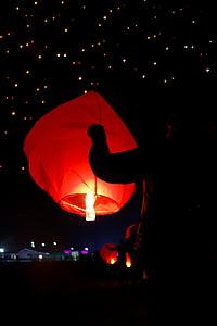 man holding lighted sky lantern at night time
