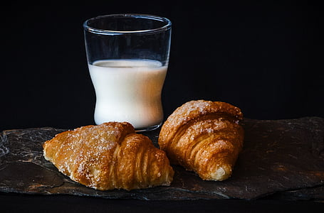 clear drinking glass with milk beside the bread