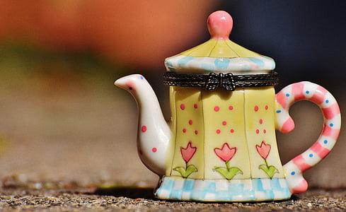 selective focus photography of yellow teapot