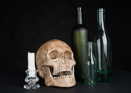 brown skull, white candle and three glass bottles