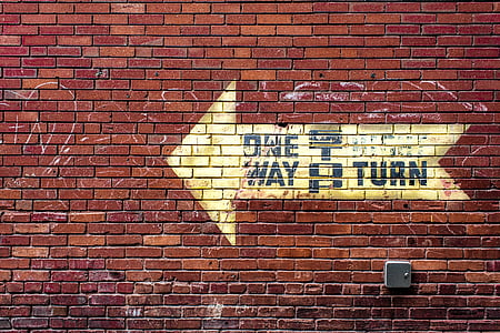 One Way signage on red brick wall