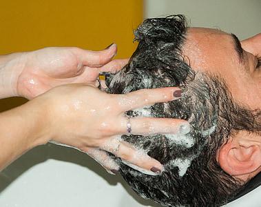 person massaging man scalp